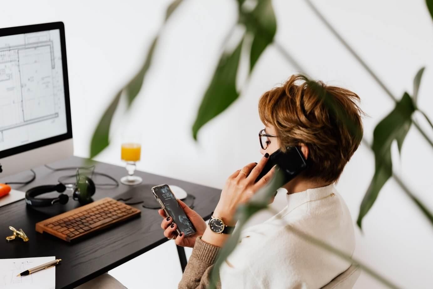 kobieta korzystająca z dwóch telefonów i komputera jednocześnie